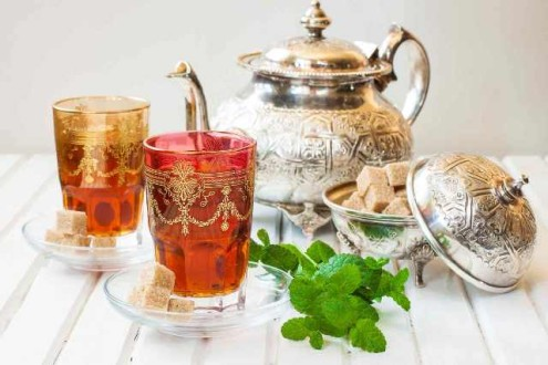 Moroccan tea with mint and sugar in a glass on a white table